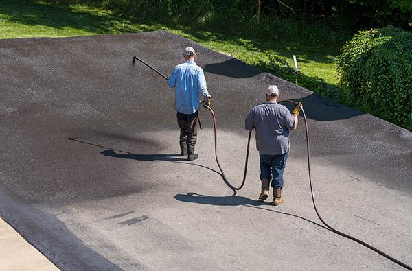 Workers spraying blacktop or asphalt sealer onto roadway